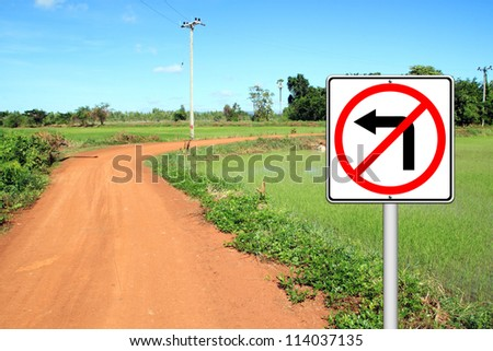 don't turn left sign with a left curved soil road