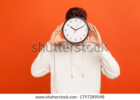 Don't waist your time! Man in casual white sweatshirt holding wall clock hiding his face, time management, schedule and meeting appointment. Indoor studio shot isolated on orange background Photo stock ©