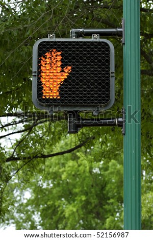 Don't walk sign with orange hand signal on pole