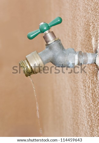 Don't waste water! Wasting water depicted by a leaking outdoor wall valve. Valve is attached to a pipe embedded in the stucco as water drips from the spout.