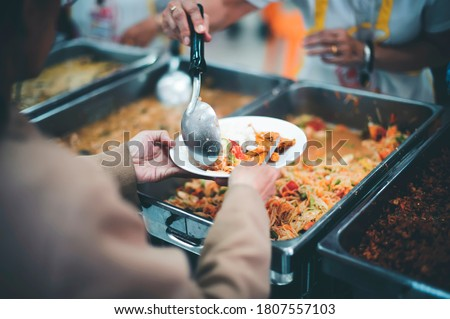 Photo of  donate food to the homeless : The hands of the poor handed a plate to receive food from volunteers to alleviate hunger
