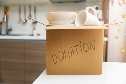 donate household items - box with tableware for donation on kitchen table