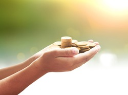Donate money concept: Business man hands holding stacks of golden coins on blurred sunset background