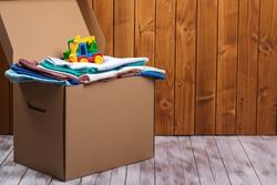 Donation box with children's things and toys. Donation box full with stuff for donate. Help poor. Case full of clothing for poor families. Sharity social activity. Cardboard box clothes for charity.