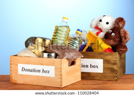Donation box with food and children\'s toys on blue background close-up