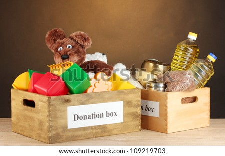 Donation box with food and children's toys on brown background close-up