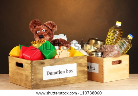 Donation box with food and children\'s toys on brown background close-up