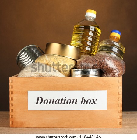 Donation box with food on brown background close-up