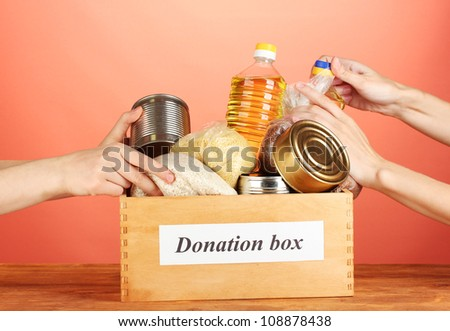 Donation box with food on red background close-up