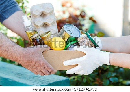 Donation box with various food. A volunteer passes a cardboard box with dry cereals, canned goods, eggs, oil. From hand to hand. Help during a pandemic. Food donations or food delivery concept. Stock photo ©