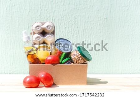 Donation box with various food. Cardboard box with oil, juice, canned foods, vegetables and citrus fruits, eggs. Food donations or food delivery concept. Help during a pandemic.