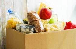 Donation box with various food. Open cardboard box with butter, canned goods, cereals and fruits.