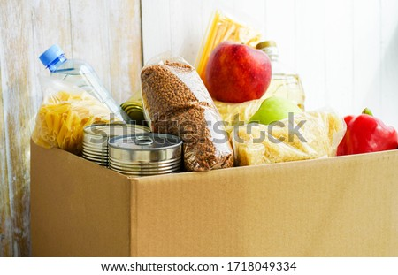 Donation box with various food. Open cardboard box with butter, canned goods, cereals and fruits. Stock photo ©