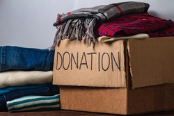 Donation concept. Donation box with donation clothes on a table. Charity. Helping poor and needy people