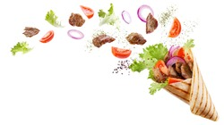 Doner kebab or shawarma with ingredients floating in the air : beef meat, lettuce, onion, tomatos, spice. White background. Copy space.