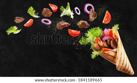 Doner kebab or shawarma with ingredients floating in the air : beef meat, lettuce, onion, tomatos, spice. Black background. Copy space.