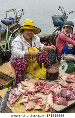DONG HOI, VIETNAM - CIRCA MARCH 2012: Couple of female butchers at open air market sitting with pieces of meat. At the bay shore displaying fresh cut raw meat on carton in the dirt.