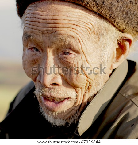 DONGCHUAN CHINA - NOVEMBER 23: Old blind Chinese man begging for money, November 23, 2010 in Dongchuan, China. China is estimated to account for over 18% of the world's blind population.