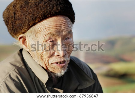 DONGCHUAN CHINA - NOVEMBER 23: Old blind Chinese man begging for money, November 23, 2010 in Dongchuan, China. China is estimated to account for over 18% of the world\'s blind population.