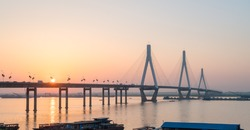 dongting lake bridge with setting sun, cable-stayed section consists of three tower supporting, China