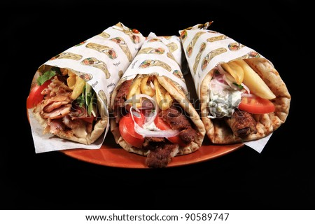 donner kebab served on a plate with pita potatoes and tzatziki sauce isolated on a black background