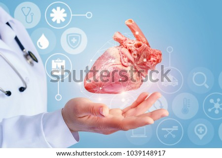 Donor heart is in the hand of the doctor on a blue background.