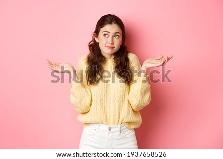 Dont know, not care. Clueless girl shrugging shoulders and looking away, avoid answering questions, have no idea, standing indecisive against pink background