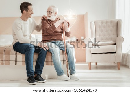 Dont worry. Pleasant handsome interested man sitting on the bed smiling and talking to his father.