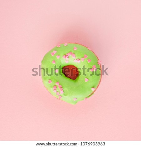 Donut covered with green glaze and sprinkled with pink hearts on pink background #1076903963