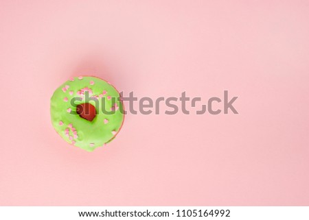 Donut covered with green glaze and sprinkled with pink hearts on pink background #1105164992