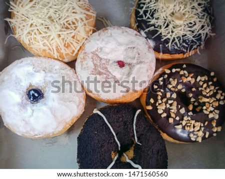 Donuts are various flavours with various toppings.