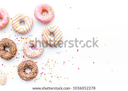 Donuts decorated icing and sprinkles on white background top view copy space pattern