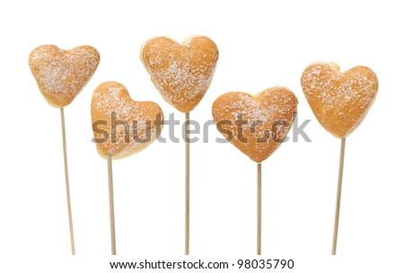 donuts heart-shaped inserted on sticks, isolated on white