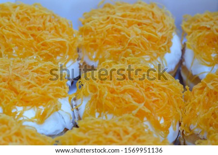 "Donuts in a paper box.Sweet donuts filling with butter cream and foi thong or gold threds. Homemade bread, homemade bakery.Thai desserts ""Foi Thong"" (golden egg yolks threads) ."