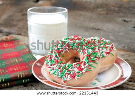 Donuts with Christmas colored sprinkles and a glass of milk in the background. Used a selective focus and shallow DOF.