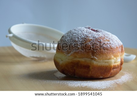 Donuts with powdered sugar and strainer on wooden table. Fat Thursday Zdjęcia stock ©
