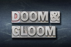 doom and gloom phrase made from metallic letterpress on dark jeans background