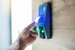 Door access control. Staff holding a key card to lock and unlock door at home or condominium. using electronic card key for access. electronic key and finger scan access control system to unlock doors