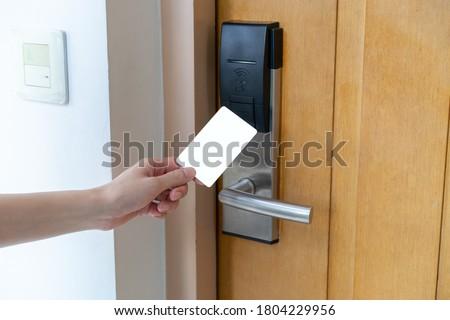 Door access control - woman hand holding white mockup key card to lock and unlock door. digital door lock.
