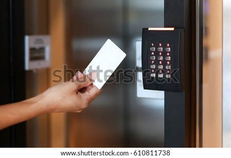 Door access control - young woman holding a key card to lock and unlock door.