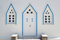 Door and windows of the Orthodox Chapel of Saint Barbara in the old town of Chora on Andros, famous Cycladic island in the heart of the Aegean Sea