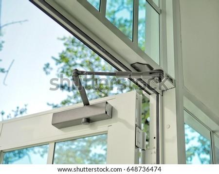 Door closer on modern glass door.