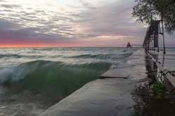 Door County Sturgeon Bay Red Lighthouse during sunrise and sunset with crashing waves on a late summer or early fall morning