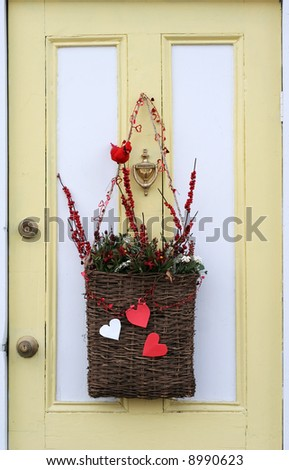 door decoration with basket holding berries, hearts and artificial cardinal