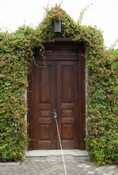 Door entrance home in Guatemala surrounded by natural leaves, rope in street.