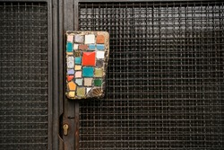 Door handle decorated with a mosaic, contrasted with an iron net covering the door