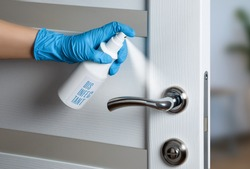 Door handle disinfection for the prevention of viral infection during the COVID-19 pandemic. White door. Door knob.