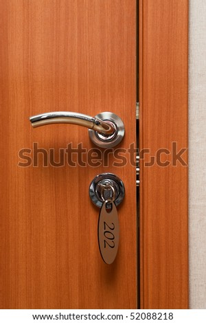 Door handles on wood wing of door and key in keyhole with numbered label
