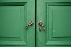 Door handles with an old double wood door green