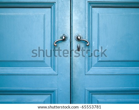 Door handles with an old double wood door painted with blue